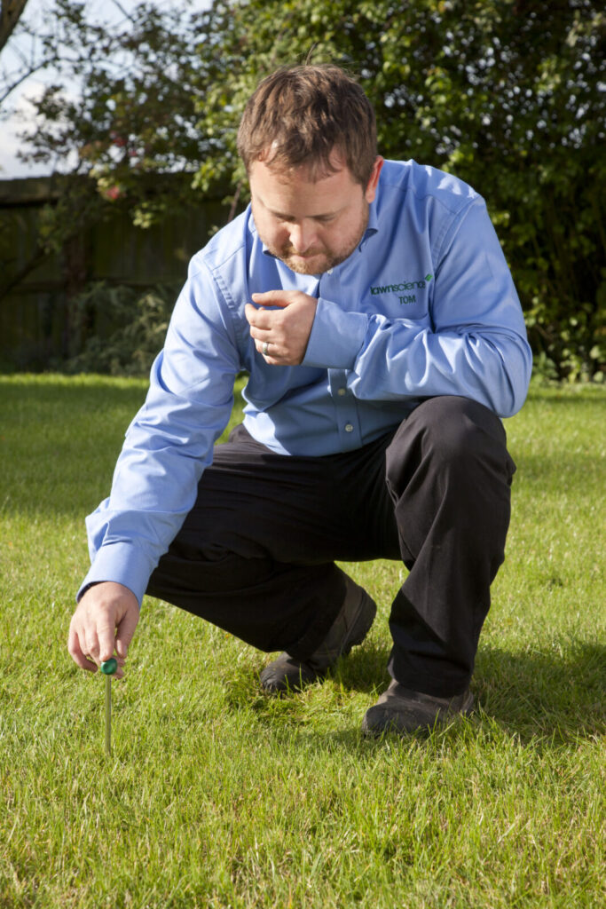 Image of lawnscience technician inspecting the condition of a lawn prior to applying an annual lawn treatment programme